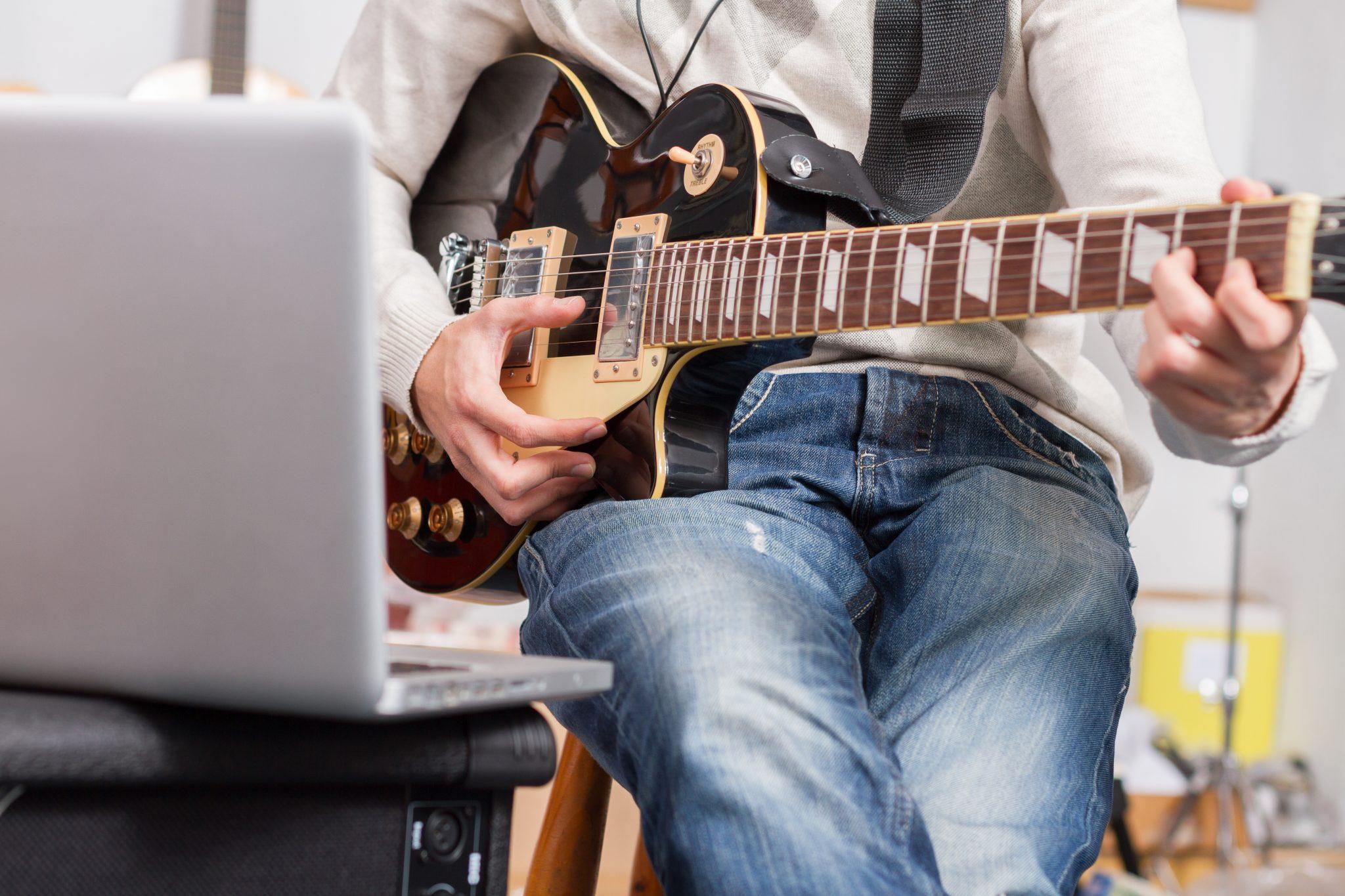 Man playing guitar for DAW