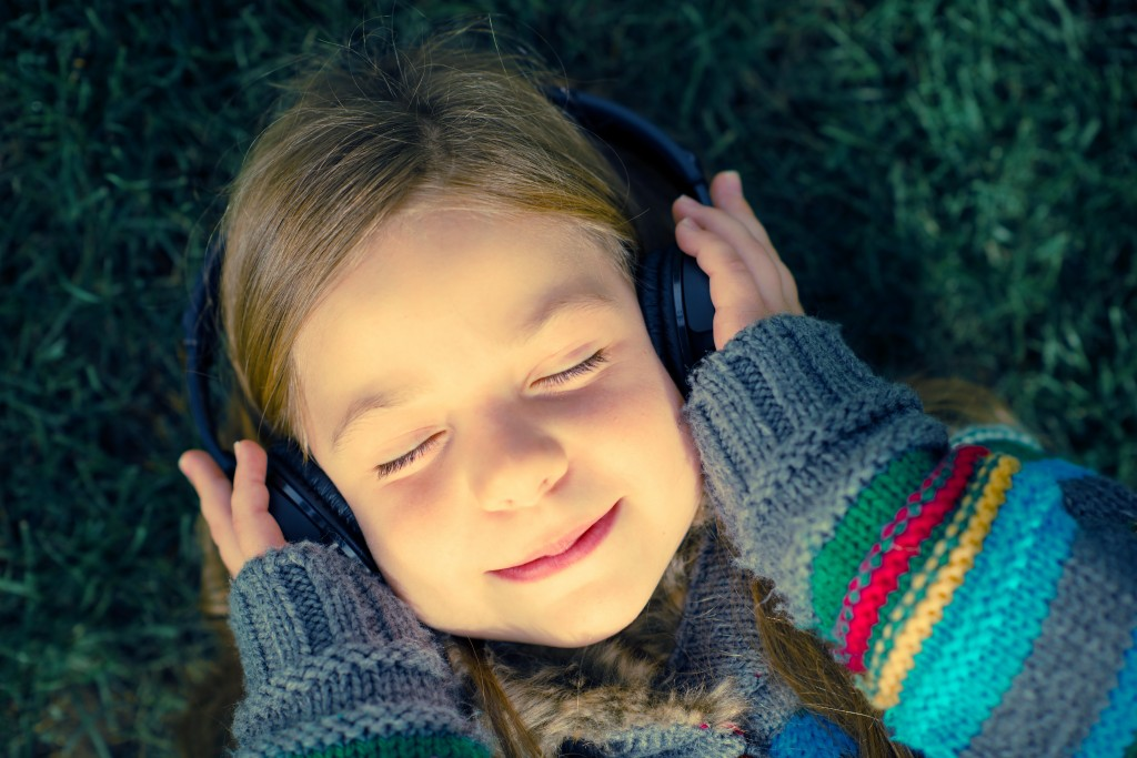 Girl with Wireless Headphones Enjoying Music Laying on Grass in a Park.